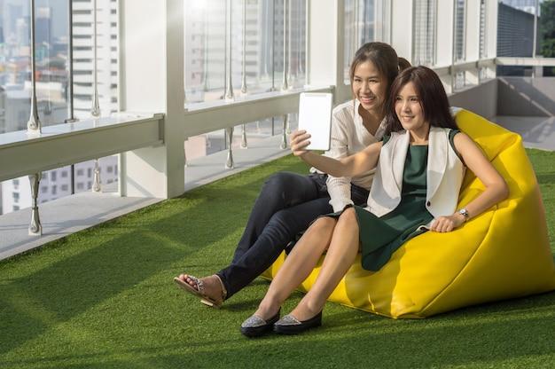 Женщины, использующие планшет, занимаются самим собой. в современном творческом офисе