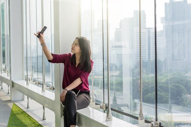 Азиатская женщина, использующая смартфон, сама себя делает в современном творческом офисе