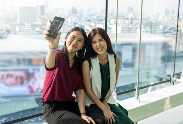 Пара азиатских женщин, использующих смартфон, делают себя самим в современном творческом офисе