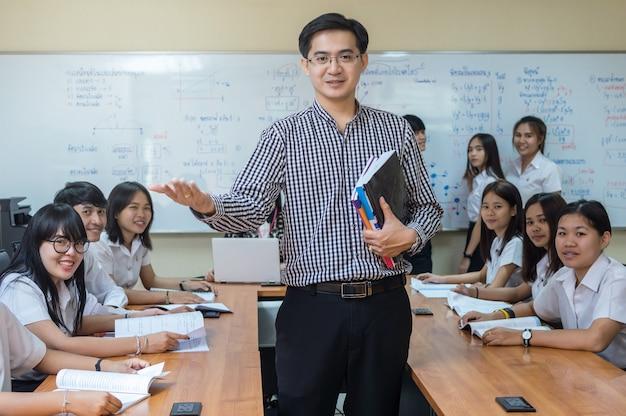 アジアの教師の肖像教室で大学生のグループにレッスンを与える