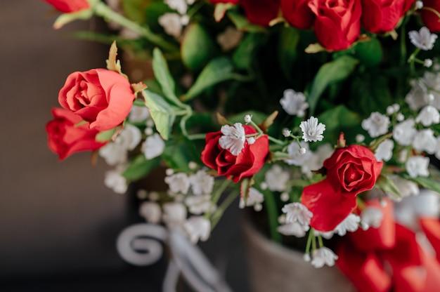 ソファの横にある赤いバラの花束