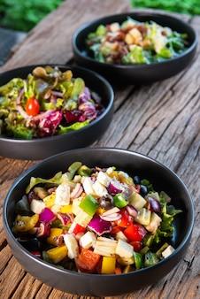 ギリシャのサラダ、日本のサラダ、シーザーサラダ、黒いセラミックボウルで、木製のテーブルで、健康愛好家、野菜愛好家のため。