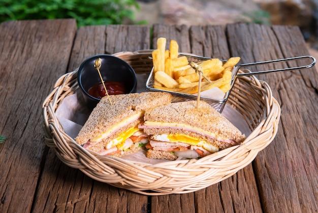 自家製小麦ハムサンドイッチ、目玉焼き、鶏肉、玉ねぎ、トマト、サラダ、ポテトチップスとトマトソース添え