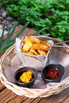 Вкусный картофель фри, подается с кетчупом и горчичным соусом. устроили в красивую ротанговую корзину, поставили на деревянный стол.