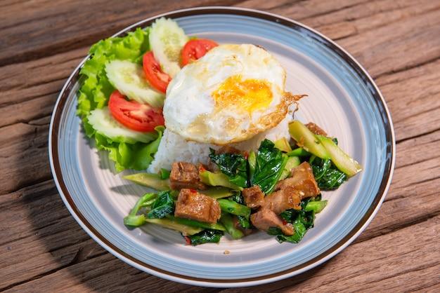カリカリのポークとフライドケールをご飯と一緒に炒め、レタス、キュウリ、トマトを添えて、美しい料理をアレンジし、木製のテーブルに置きます。