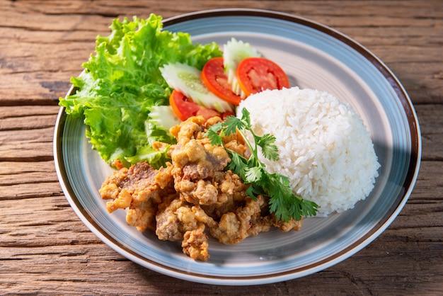 ご飯をのせた豚肉の炒め物、レタス、キュウリ、トマトを添えて、美しい料理をアレンジし、木製のテーブルに置きます。