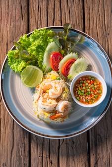 美味しい海老チャーハン。新鮮な唐辛子とキュウリのトマトサラダを添え、木製のテーブルに置いた美しい皿に並べます。