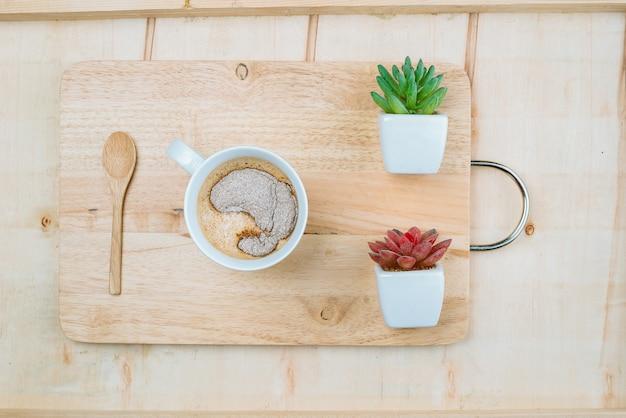 Сладкая чашка кофе на деревянной тарелке, украшенной двумя растениями