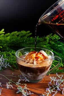 コーヒーをトッピングしたガラスのカップにあるバニラアイスクリームは完璧です。