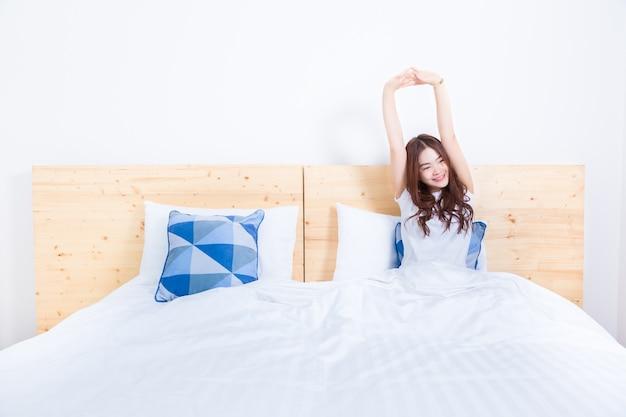 Молодой улыбается счастливый азии женщина, просыпаться, растяжения, в ее белой кровати