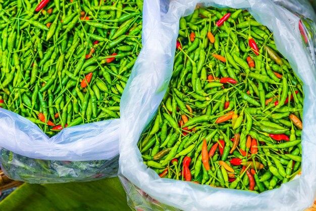 Сумки свежего зеленого и красного пряного тайского чили на местном свежем рынке