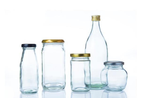 白い背景に蓋を付けて様々なサイズと形の透明なガラス瓶