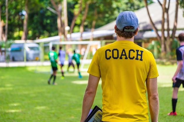彼のチームの試合を見ているサイドラインに立っている男性サッカーまたはフットボールのコーチ