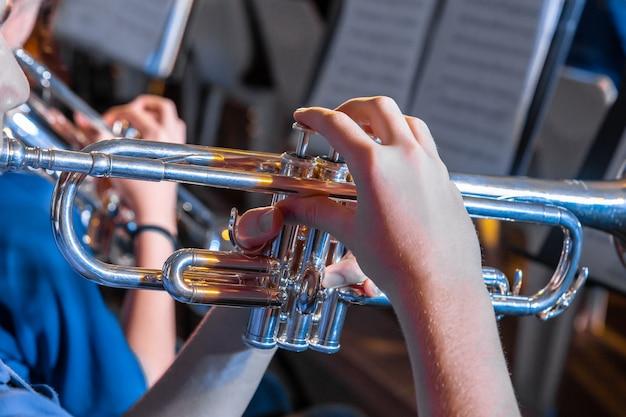 ローカルのバンドコンサートでトランペットを持ち、演奏している男性ミュージシャンの手