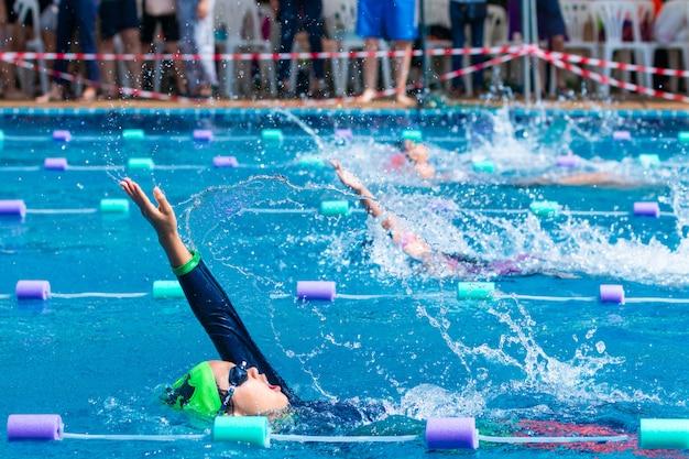 Молодые пловцы, тренирующиеся в бассейне, плавают в бассейне