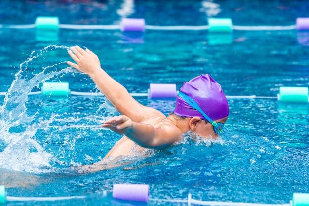 彼の蝶ストロークを練習している若い男の子の水泳