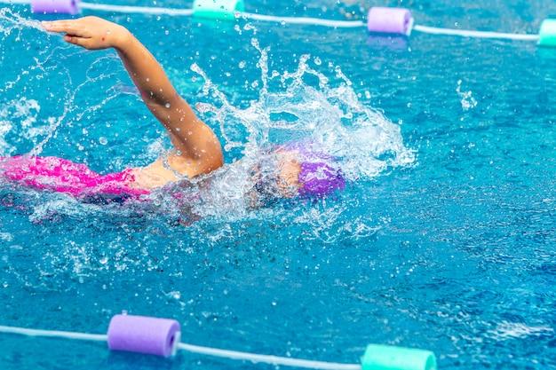 彼女のフリースタイルで働く若い女の子の泳者は、地元のプールで泳ぐ