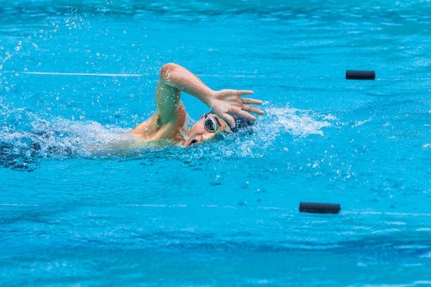 地元のプールでフリースタイルのスイミングストロークをやっている男性の水泳選手