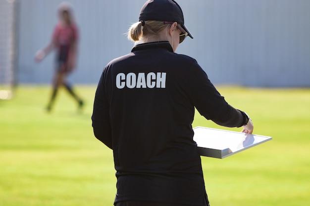 屋外スポーツフィールドで黒いコーチシャツの女性スポーツコーチの背面図