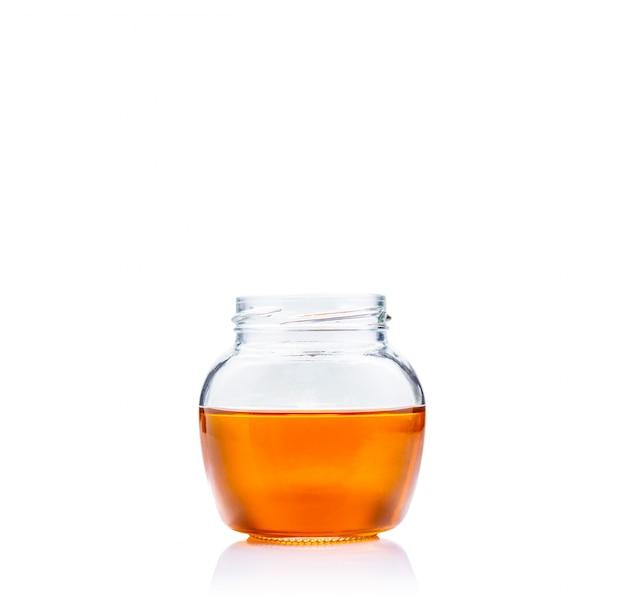 コピースペースと白い背景の上のガラスの瓶に蜂蜜します。