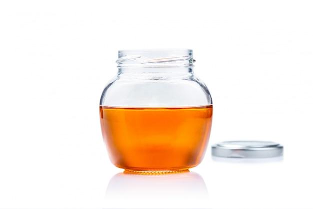 コピースペースと白い背景の上の蜂蜜のガラス瓶