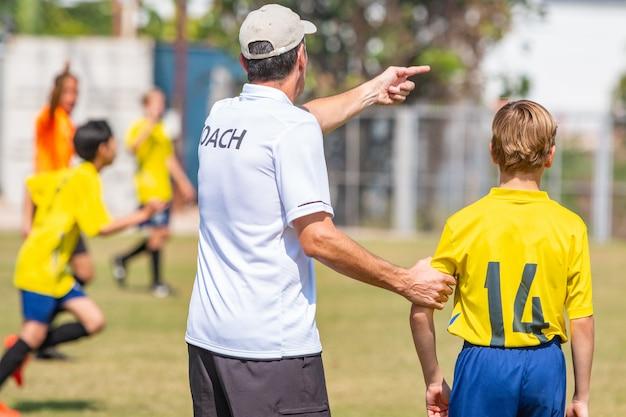 Задняя часть мужского футбольного тренера собирается отправить в игру своего молодого мальчика
