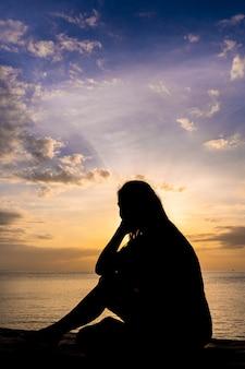 海の上のカラフルな日の出を見ている女性のシルエット