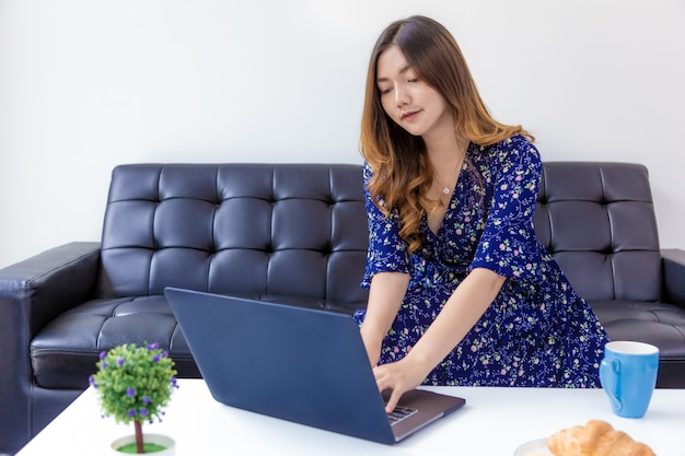 彼女の自宅のリビングルームで彼女のコンピューターに取り組んでいる青いドレスの若い美しい女性