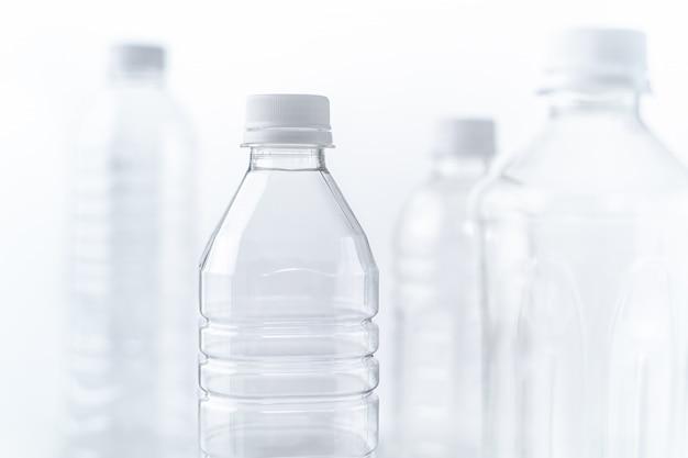 さまざまな形やサイズの白いテーブルと背景のペットボトル