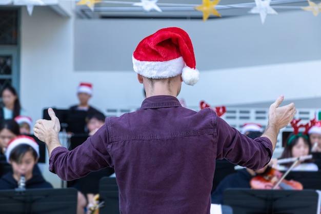 Вид сзади мужского дирижера, одетого в повседневную одежду с красной шляпой санты, проводящего свою молодую группу, исполняющую рождественскую музыку на мероприятии на открытом воздухе