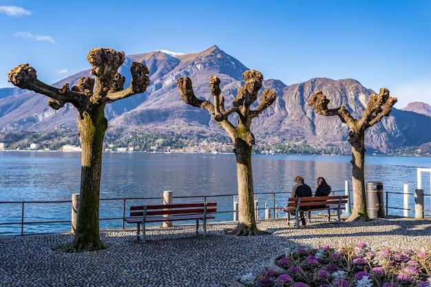人々はベンチに座って、イタリア、ヴァレンナのコモ湖周辺の美しい風景の眺めを楽しみます