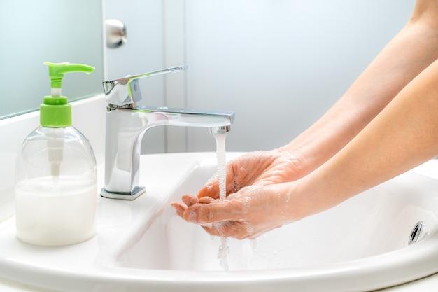 良い衛生と清潔のために流しで石鹸で手を洗う女性