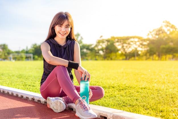 幸せな美しい若いアジア女性はランニングトラックで彼女の朝の運動中に休憩するために停止します