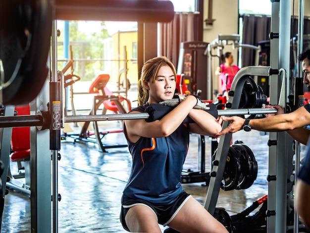 Тренировка женщины и потеря веса на спортзале фитнеса