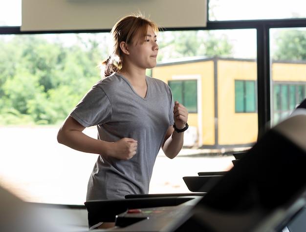 Женщина работает на электрической беговой дорожке в тренажерном зале