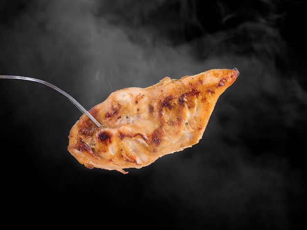 黒の背景のスタジオで煙と鶏の呼吸グリル