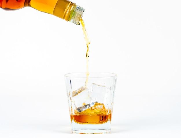 白い背景の上の冷たい氷とウイスキーのグラス