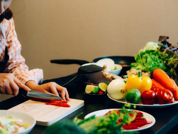 アジアの美しい女性の間に台所でスパゲッティ料理を作る
