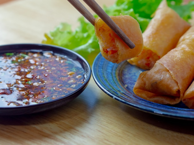 タイ春巻き、豚肉、鶏肉のスライス、スパイシーなソースが付いているオイルの火
