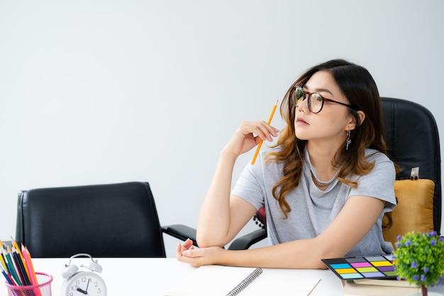 Азиатская женщина с длинными золотыми волосами в очках, сидя за столом