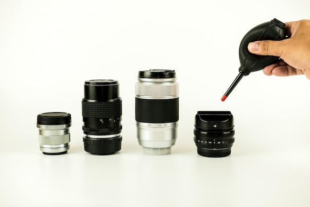カメラのレンズのクリーニング方法は、白い背景の上の人間の写真でフォーカスを閉じる