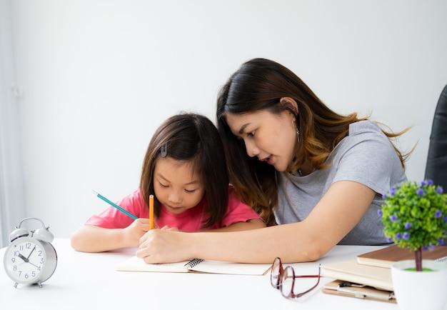 Молодая женщина учит домашнее задание для своего ребенка дома