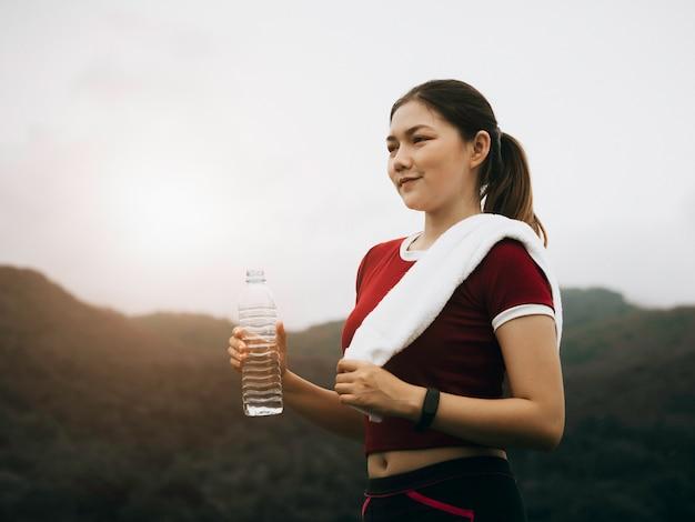 美しいアジアの女性は外で運動し、水を飲む