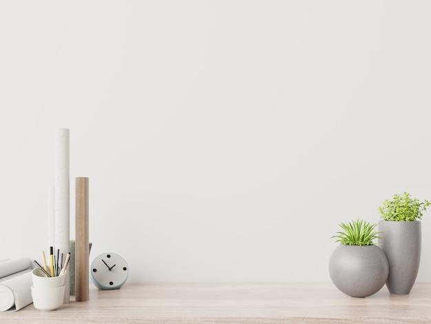 植物と創造的な机と現代の職場には白い壁があります。