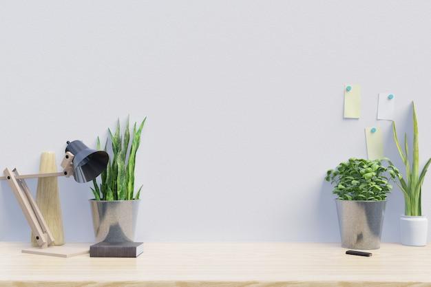 植物のある創造的な机のある現代の職場には白い壁があります