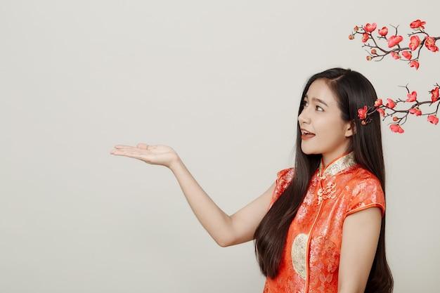梅の花と伝統的な中国の赤いドレスの女性