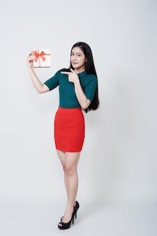 Женщина, держащая подарочную коробку рождество на белом