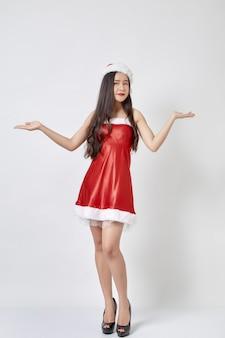Молодая азиатская женщина в шляпе санты на белизне