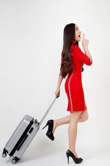 スーツケースと赤いドレスの女