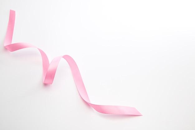 白で隔離されるピンクの巻きリボン